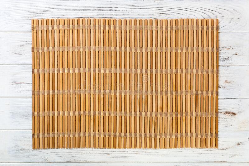 Empty Asian Food Background. brown Bamboo mat on wnite wooden background top view with copy space flat lay. Empty Asian Food Background. brown Bamboo mat on stock images