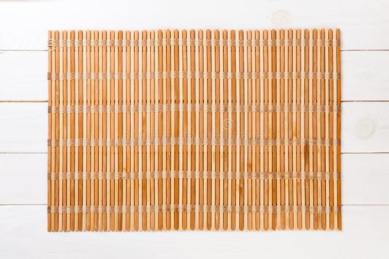 Empty Asian Food Background. brown Bamboo mat on wnite wooden background top view with copy space flat lay. Empty Asian Food Background. brown Bamboo mat on stock photos