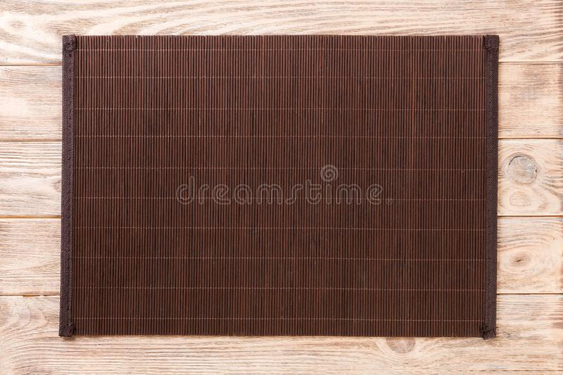 Empty Asian Food Background. Dark Bamboo mat on brown wooden background top view with copy space flat lay. Empty Asian Food Background. Dank Bamboo mat on brown royalty free stock image