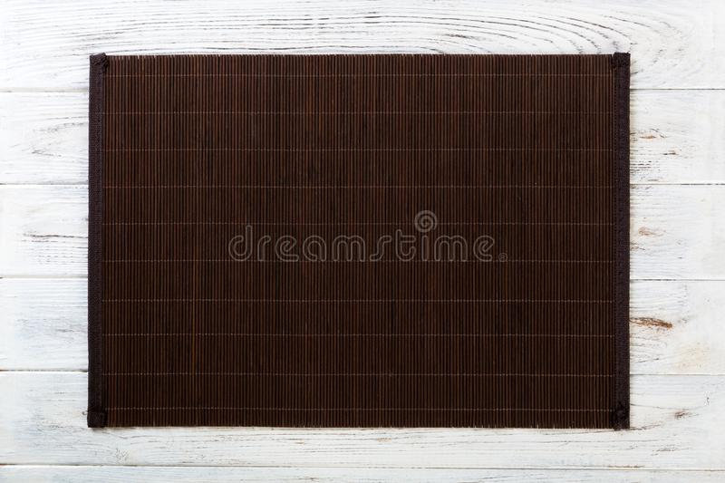 Empty Asian Food Background. Dark Bamboo mat on white wooden background top view with copy space flat lay. Empty Asian Food Background. Dank Bamboo mat on wooden stock images