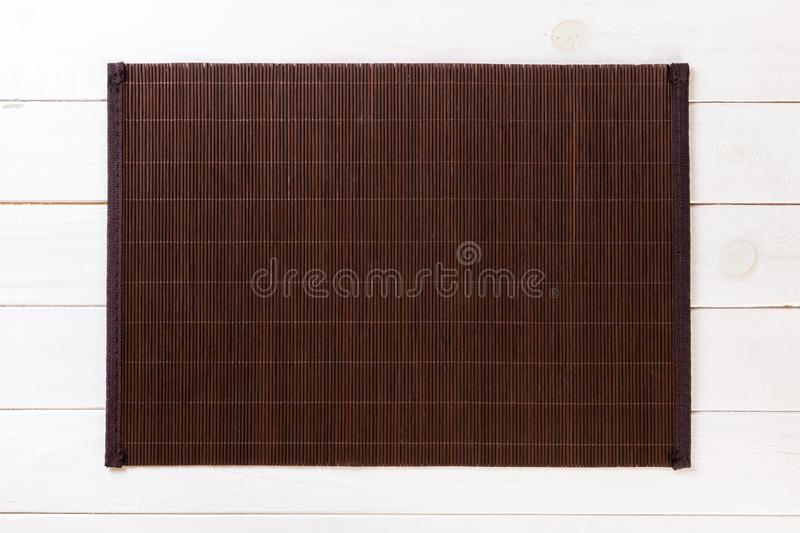 Empty Asian Food Background. Dark Bamboo mat on white wooden background top view with copy space flat lay. Empty Asian Food Background. Dank Bamboo mat on wooden royalty free stock photo