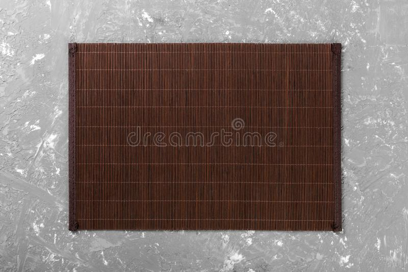 Empty Asian Food Background. Dark Bamboo mat on wooden background top view with copy space flat lay. Empty Asian Food Background. Dank Bamboo mat on wooden stock photos