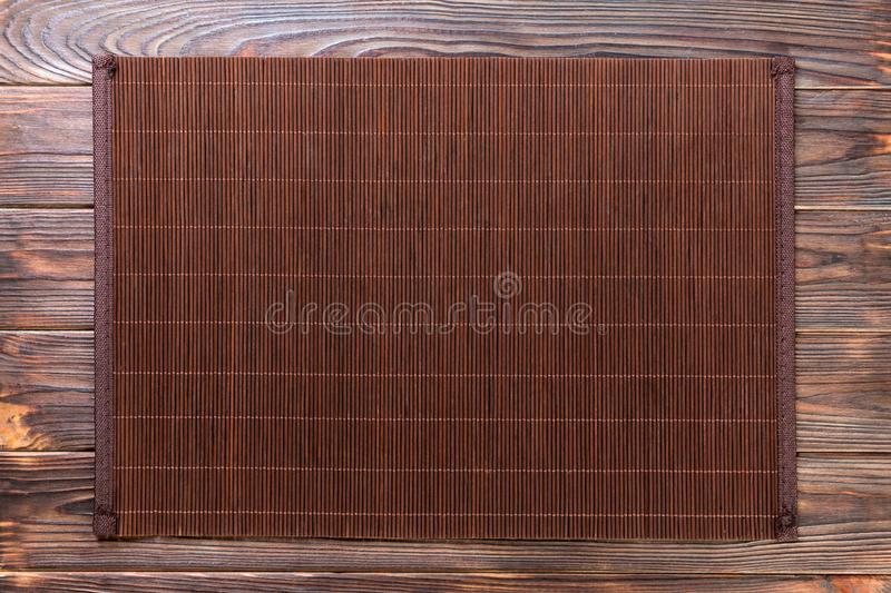 Empty Asian Food Background. Dark Bamboo mat on wooden background top view with copy space flat lay. Empty Asian Food Background. Dank Bamboo mat on wooden stock photo
