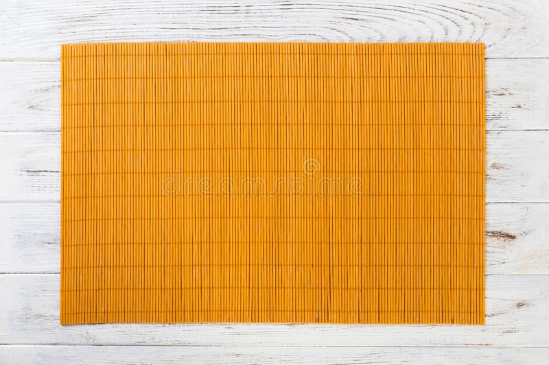 Empty Asian Food Background. Yellow Bamboo mat on wooden background top view with copy space flat lay.  stock photos