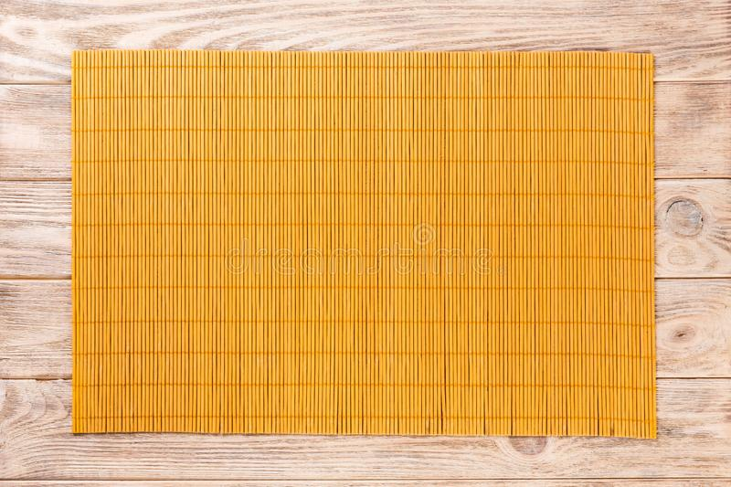 Empty Asian Food Background. Yellow Bamboo mat on wooden background top view with copy space flat lay.  royalty free stock images