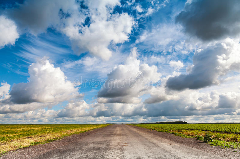Empty asphalt country road with dramatic cloudy sky royalty free stock photos