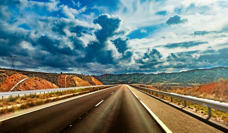 Empty asphalt highway and cloudy storm sky royalty free stock images