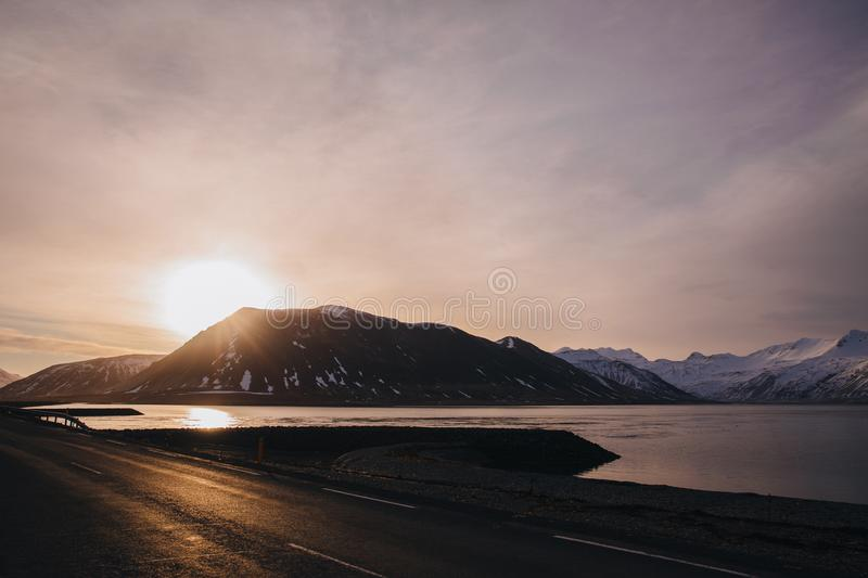 Empty asphalt road, calm water of gulf and snow-covered mountains at sunset. In iceland stock photo