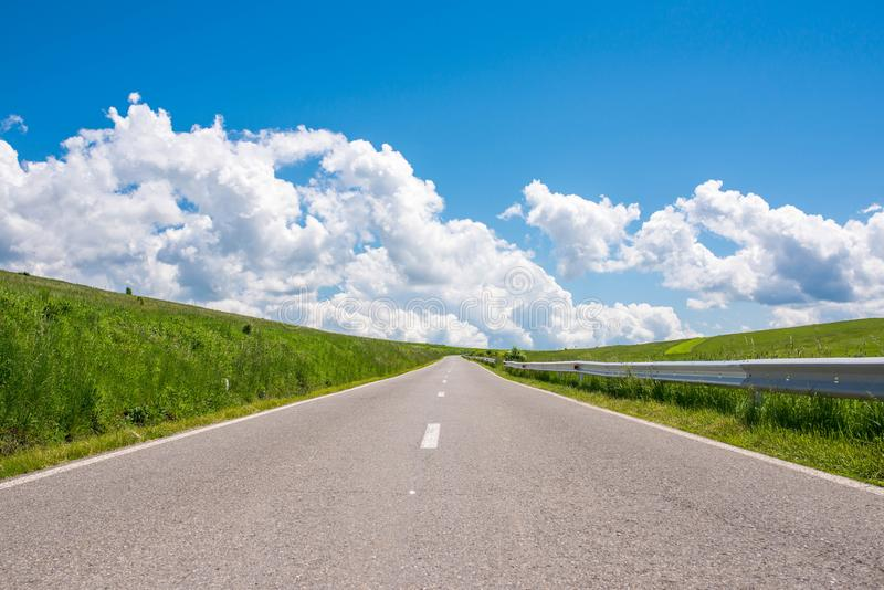 Empty asphalt road , countryside at springime, beautiful blue sky with white clouds. On the background stock photos