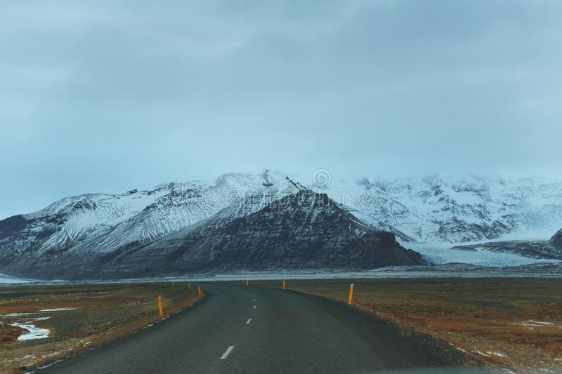 Empty asphalt road and majestic snow-covered rocky mountains. In iceland royalty free stock images