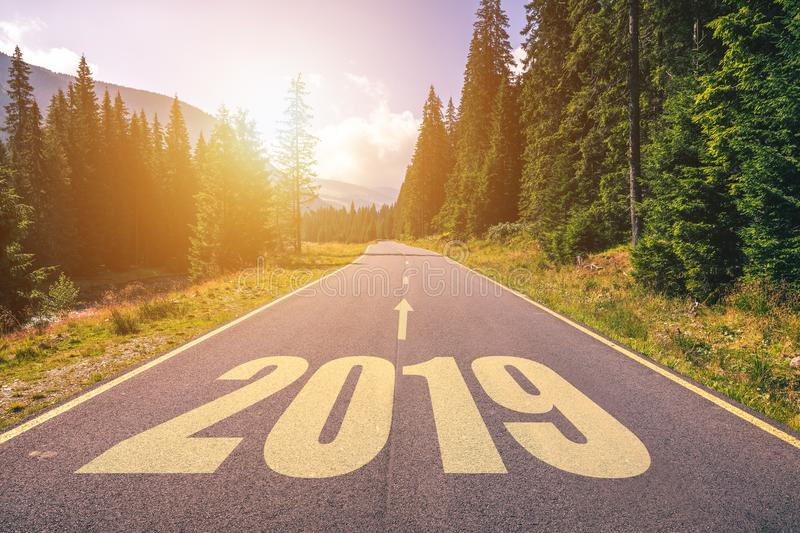 Empty asphalt road and New year 2019 concept. Driving on an empty road in the mountains to upcoming 2019 and leaving behind old 2. 018. Concept for success and royalty free stock photo