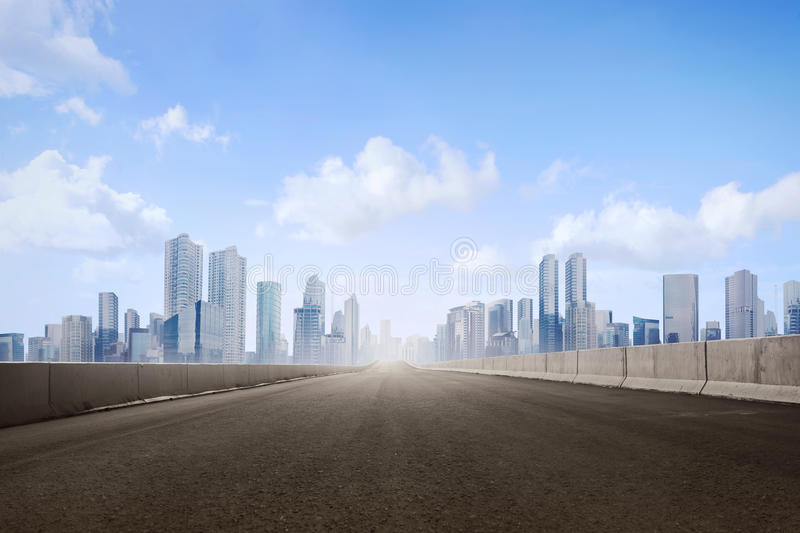 Empty asphalt road and skyscrapers in modern city. With blue skyline royalty free stock image