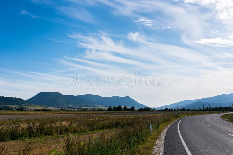 Empty asphalt road, vulcanic mountains against beautiful blue sky. With white clouds near Tusnad Bai in Transylvania, Romania stock photography