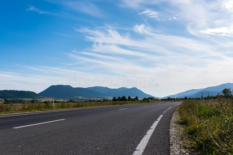 Empty asphalt road, vulcanic mountains against beautiful blue sky. With white clouds near Tusnad Bai in Transylvania, Romania stock image