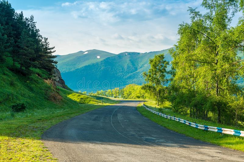 Empty automobile mountain road on a sunny summer day in the picturesque mountains of Transcaucasia royalty free stock images