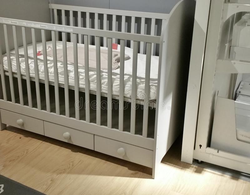 Empty baby crib. Baby crib and cabinet in a nursery royalty free stock photography