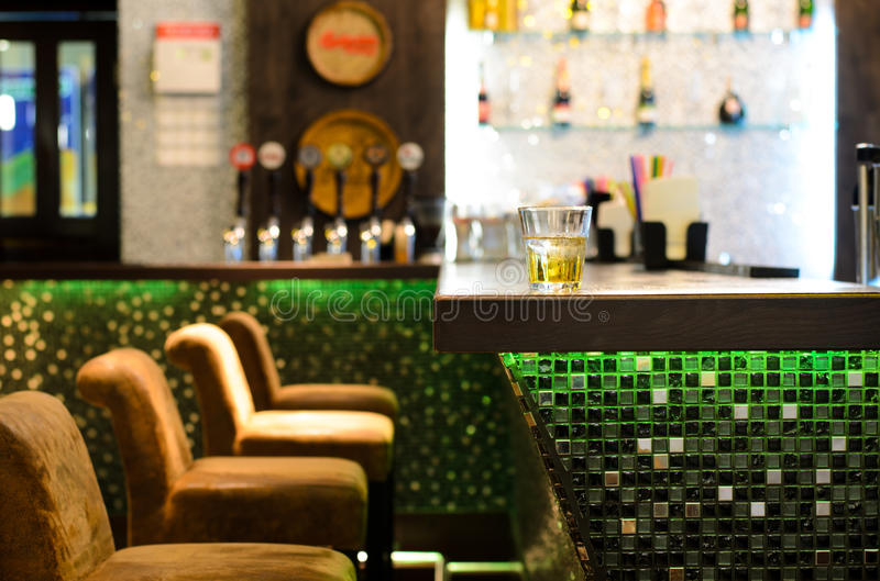 Empty bar with a tumbler of whiskey on the counter. In front of a row of empty seats with the beer taps and bottles on shelves in the background royalty free stock image