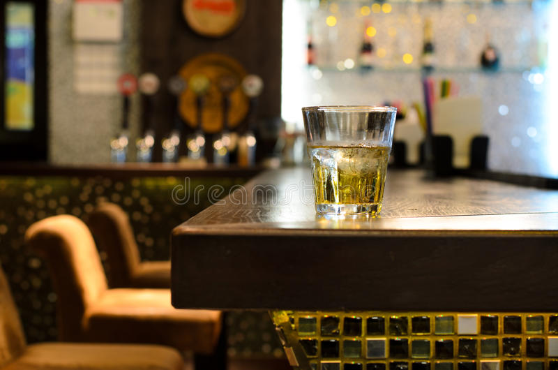Empty bar with a tumbler of whiskey on the counter. In front of a row of empty seats with the beer taps and bottles on shelves in the background royalty free stock photos