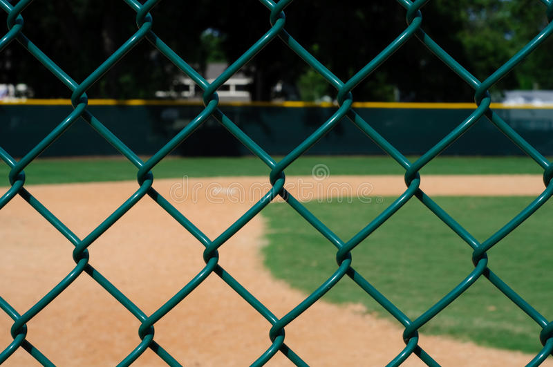 Empty Baseball Field through Fence. Looking at Empty Baseball Field through a Green Chain Link Fence stock images
