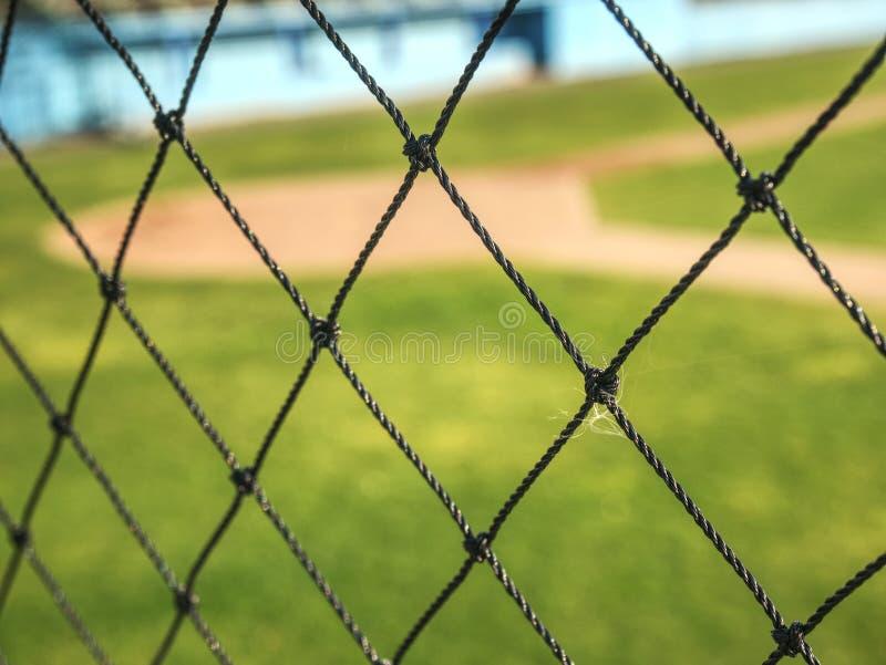 Empty baseball green field view grandstand. View through safety net around baseball field on sunny day urban team suburb street stadium sport soccer seashell stock images