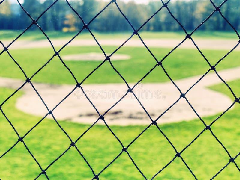 Empty baseball green field view grandstand. View through safety net around baseball field on sunny day urban team suburb street stadium sport soccer seashell stock photos