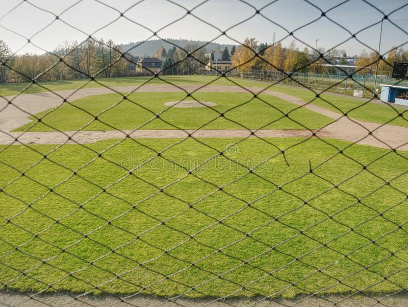 Empty baseball green field view grandstand. View through safety net around baseball field on sunny day stock image