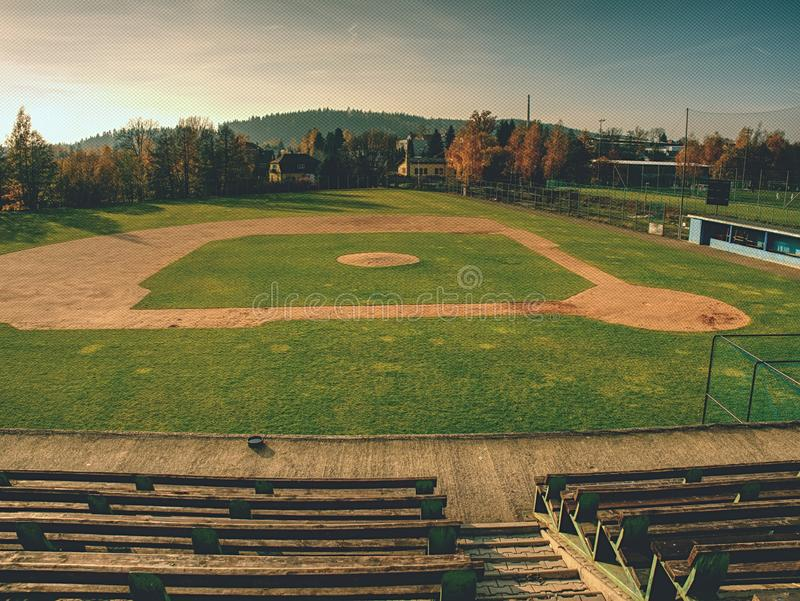 Empty baseball green field view grandstand. View through safety net around baseball field on sunny day royalty free stock image