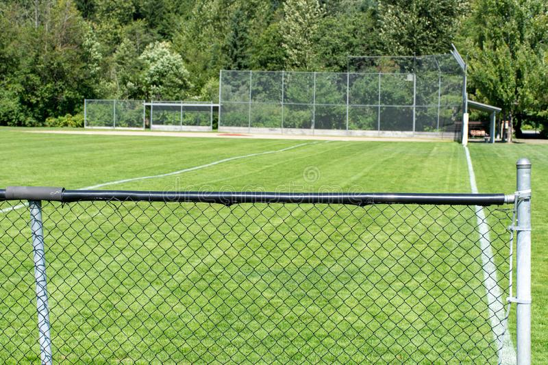 Empty baseball or softball diamond from the back fence and foul line looking towards the grass and trees in Whistler, British. Columbia, Canada royalty free stock image