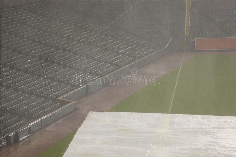 Empty baseball stands in rain delay. Empty seats in baseball stadium stands during thunderstorm delay with tarp covering infield stock image