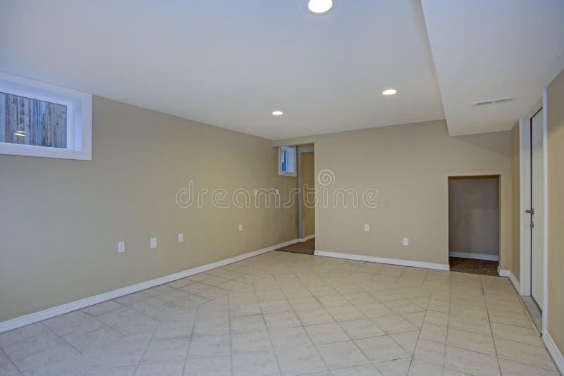 Empty room, sand beige walls, tiled floor in a luxury home. Empty basement room, sand beige walls, tiled floor in a luxury home stock photos