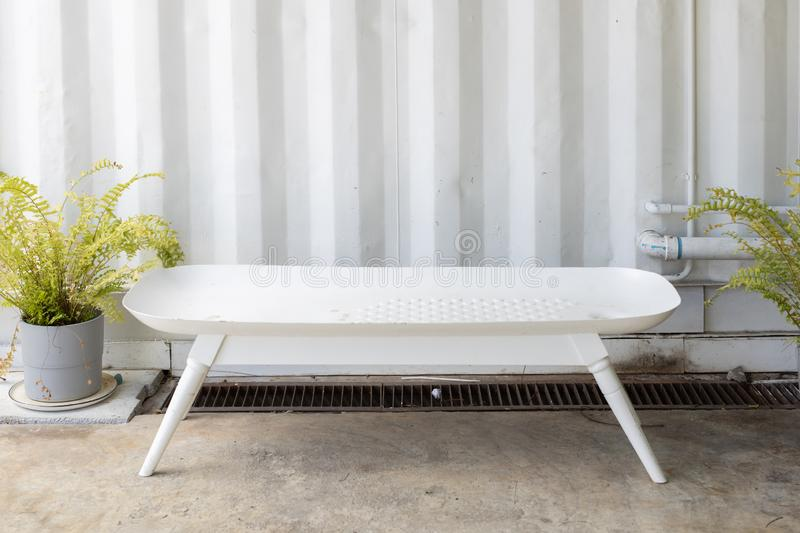 Empty bathtub bench or tub seat with sheet metal corrugated wall background royalty free stock images