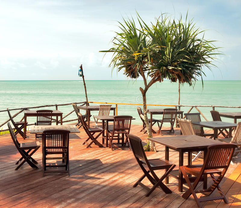 Empty beach cafe. Beach cafe with wooden tables and chairs placed at the sea waterfront royalty free stock image