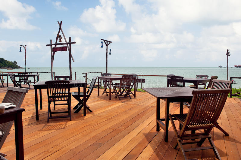Empty beach cafe. Beach cafe with wooden tables and chairs placed at the sea waterfront royalty free stock photos