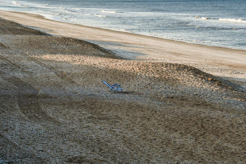 Empty Beach Chair Center Stage. An empty beach lounge chair centered in a view on Vilano Beach near St Augustine, Florida, with evening shadows on it and the stock images