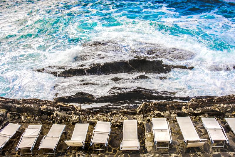 Empty beach chair deckchairs sunloungers on cliff rocks stormy sea. Waves above view rough sea background copyspace royalty free stock image