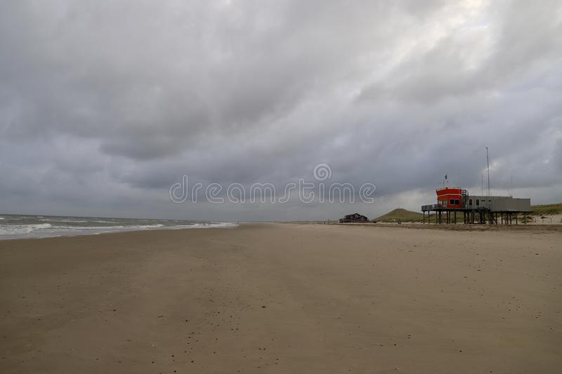 Empty beach on a cloudy day in the quiet coastal small town, the Netherlands. Lifesaving station on a background stock photography