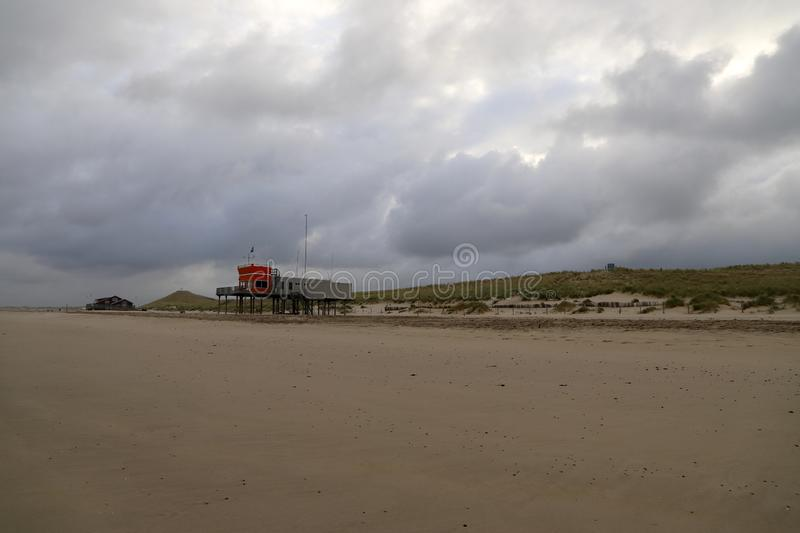 Empty beach on a cloudy day in the quiet coastal small town, the Netherlands. Lifesaving station on a background stock image