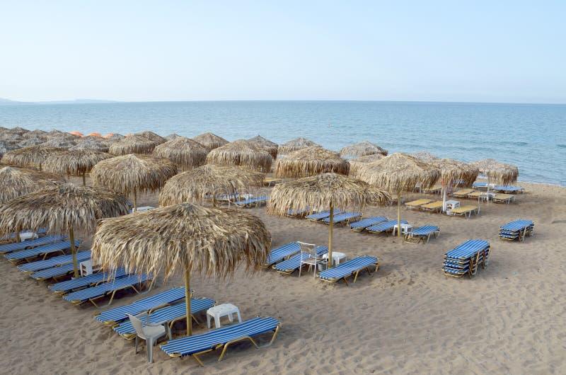 Empty beach. With deckchairs and straw umbrellas in Kourouta beach, Amaliada Greece royalty free stock photo