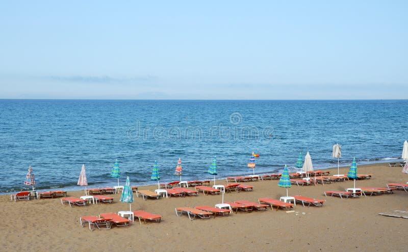 Empty beach. With deckchairs and sunshade umbrellas in Kourouta, Amaliada, Greece stock image
