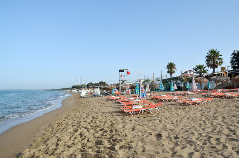 Empty beach. With deckchairs and sunshade umbrellas and lifeguard tower in Kourouta, Amaliada Greece royalty free stock images