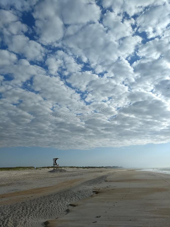 Empty beach. Wrightsville, eastcoast, wilmingtonnc, northcarolina, wooly, louds, white, clouds, stratocumulus, lifeguard, stand, popular, big, skies, seaside royalty free stock photography