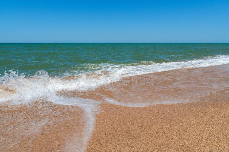 Empty beach with golden sand and azure water. Scene stock photo