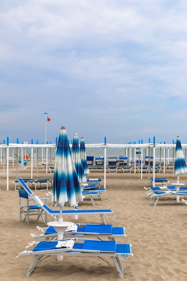 Empty beach, Italy, Riccione. Empty beach with sunbeams and umbrella royalty free stock photos