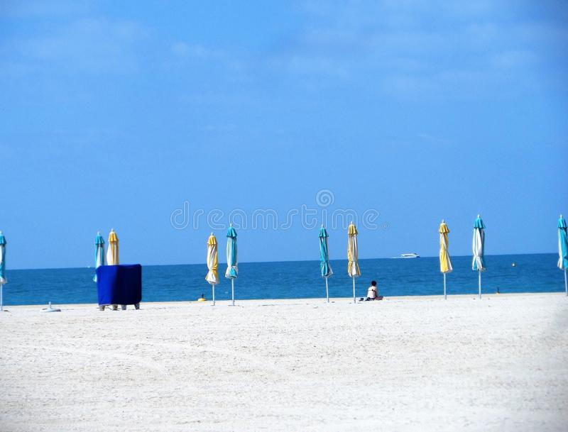 Empty beach. A lonely man is sitting on the beach. Empty beach with loungers and closed parasols stock photo