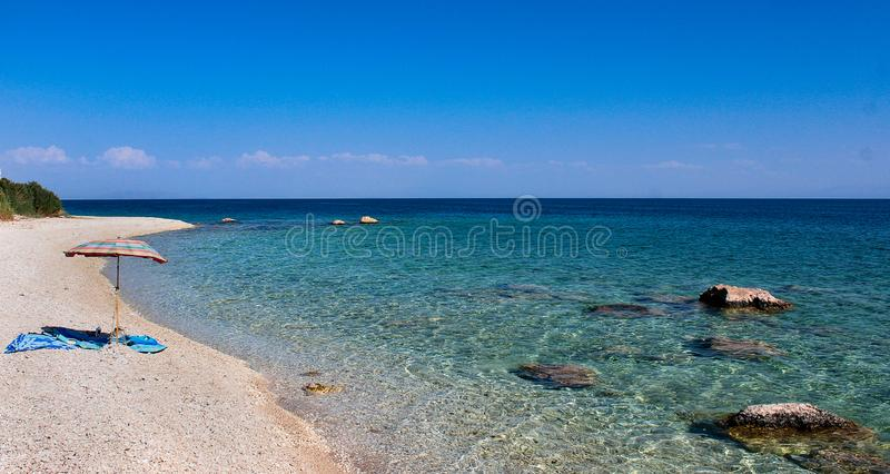 Empty beach with turquoise water and one parasol. royalty free stock images