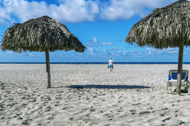Empty beach, two beach umbrellas, a chaise longue, the figure of a man walking to the sea, traces of people in the sand, royalty free stock photography
