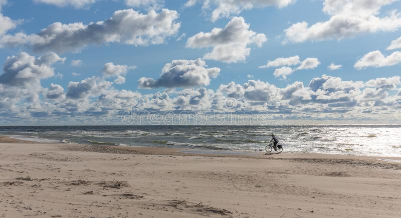 Empty beach under cloudy sky with lonely biker riding royalty free stock photography