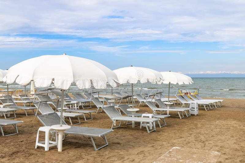Empty beach with white sunshades against the sky, Italy, Riccione stock photography