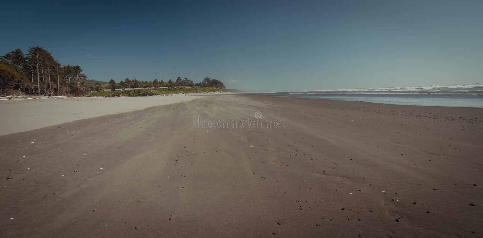 Empty beach with windy sand blowing. Down the beach royalty free stock photo