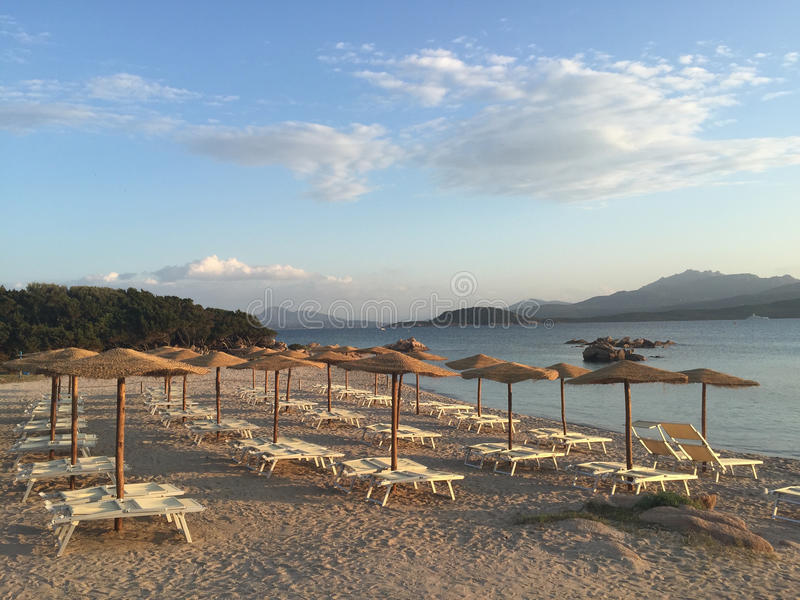 Empty beach. An empty beach with wooden umbrellas and lounge chairs, in Sardinia Italy stock image